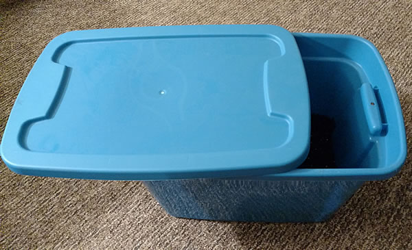 A blue plastic storage tub with soil in it and the cover covering about two thirds of the tub